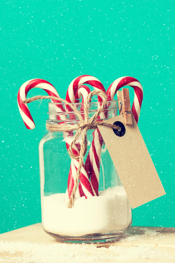 Красочные тросточки конфеты в опарнике с сахаром на деревянной предпосылке стоковая фотография