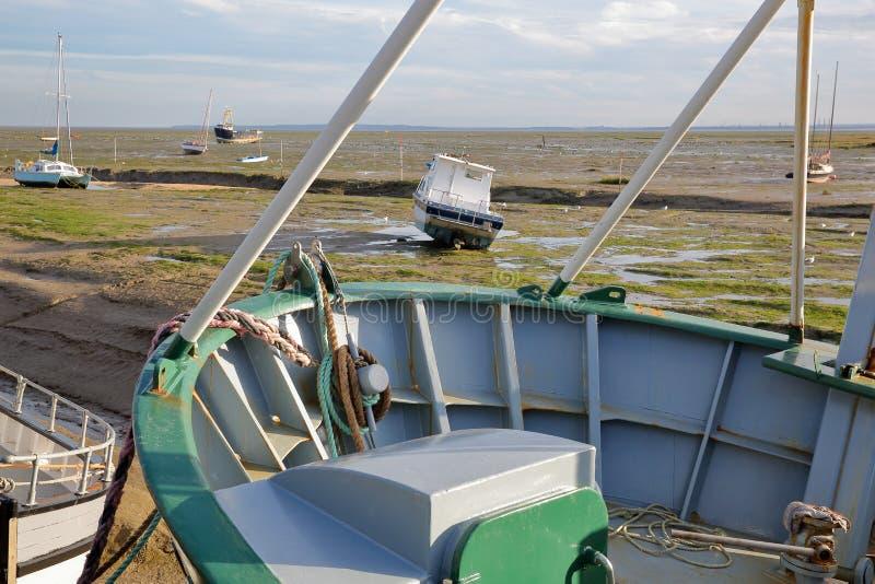 Красочные удя траулеры причаленные на набережной с грязным пляжем во время отлива на заднем плане, Leigh на море стоковые изображения rf