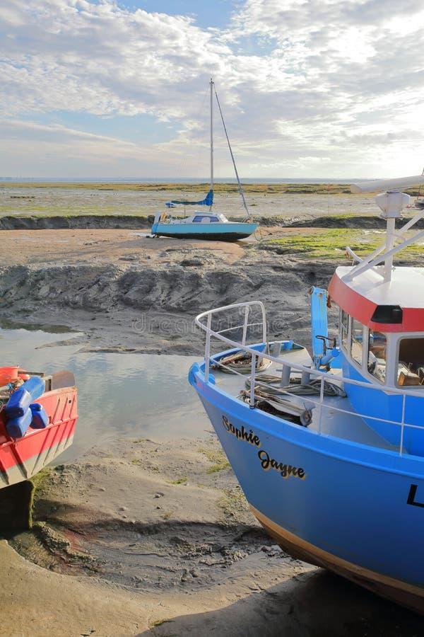 Красочные удя траулеры причаленные на набережной с грязным пляжем во время отлива на заднем плане стоковое фото rf