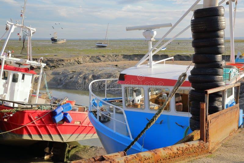 Красочные удя траулеры причаленные на набережной с грязным пляжем во время отлива на заднем плане, Leigh на море стоковое фото rf