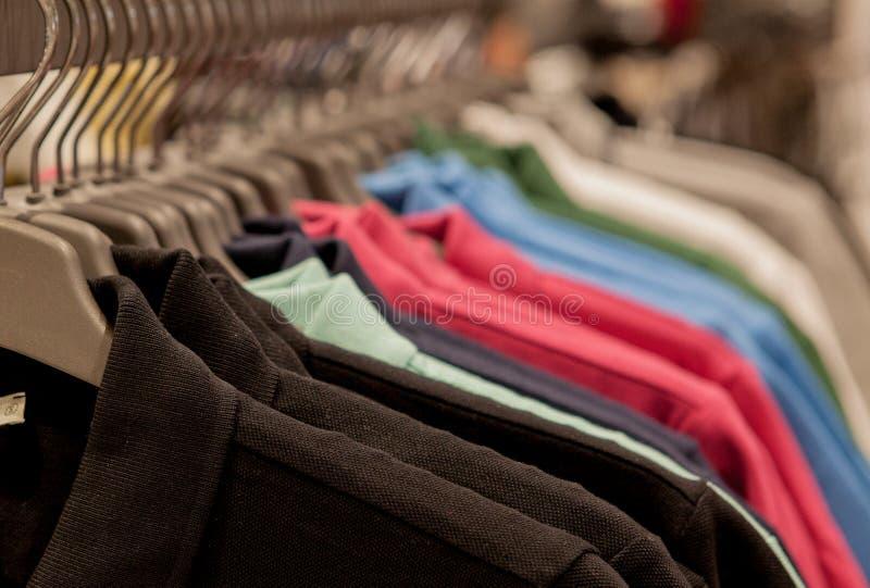 Красочные футболки на вешалках Одежды ` s людей стильные Витрина, продажа, ходя по магазинам Концепция моды и торговли стоковые изображения rf