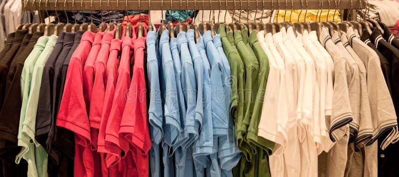 Красочные футболки на вешалках Одежды ` s людей стильные Витрина, продажа, ходя по магазинам Концепция моды и торговли стоковое изображение rf