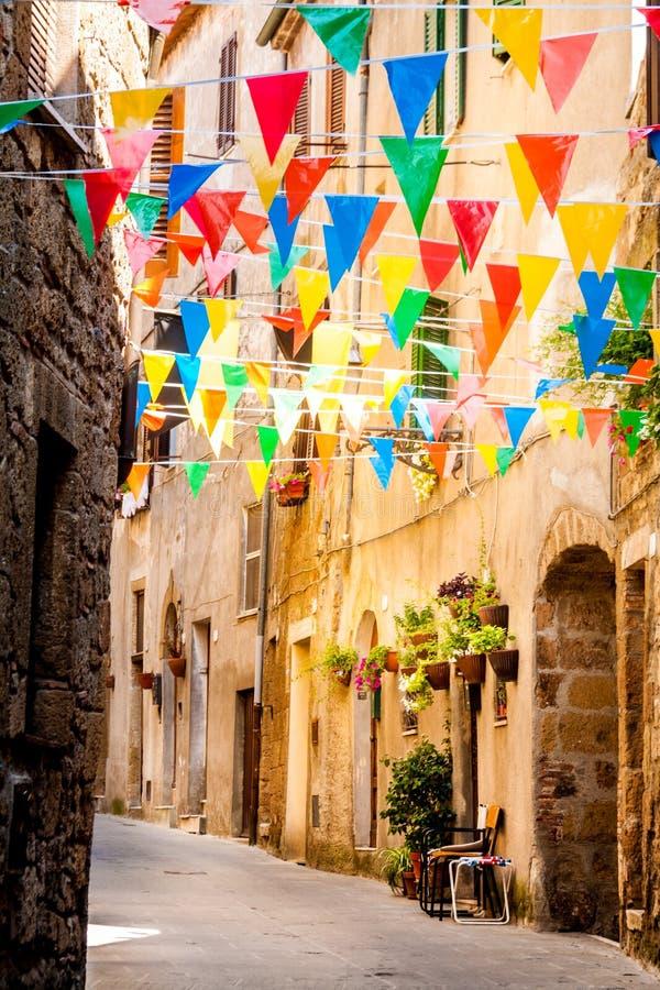 Красочные флаги партии развевают в маленьком переулке стоковая фотография