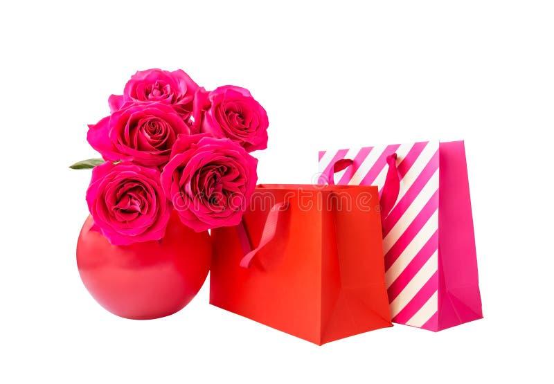 Красочные хозяйственные сумки и розовые розы изолированные на белизне стоковые фотографии rf