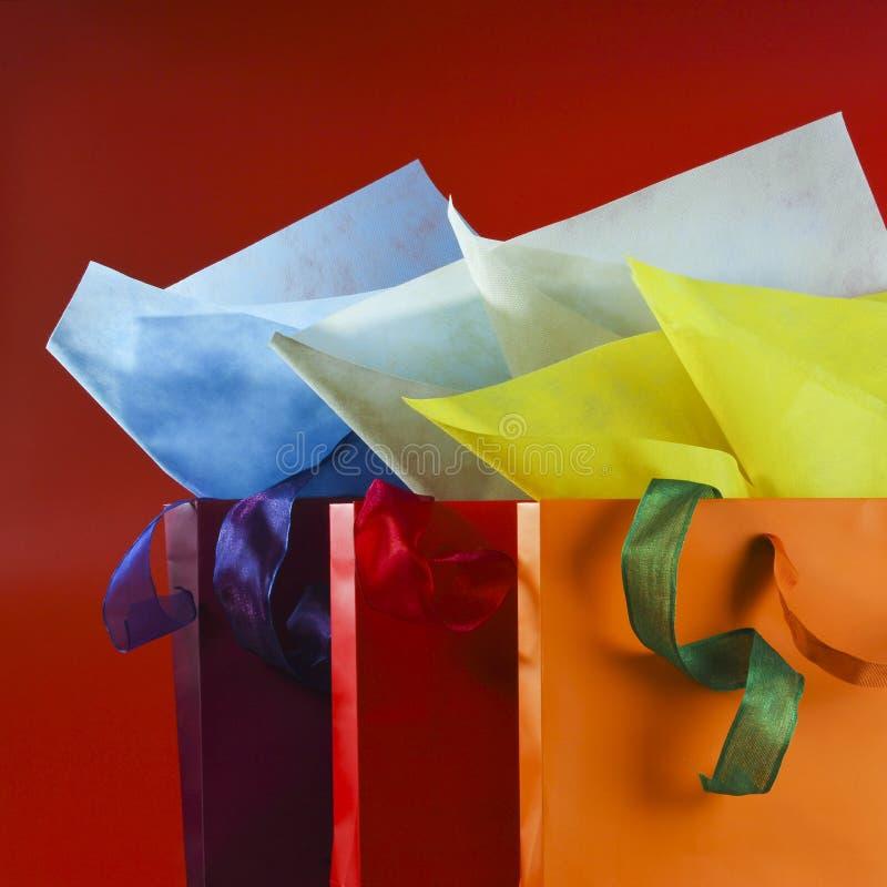 Красочные хозяйственные сумки с красочными упаковочными бумагами и лентами стоковое изображение