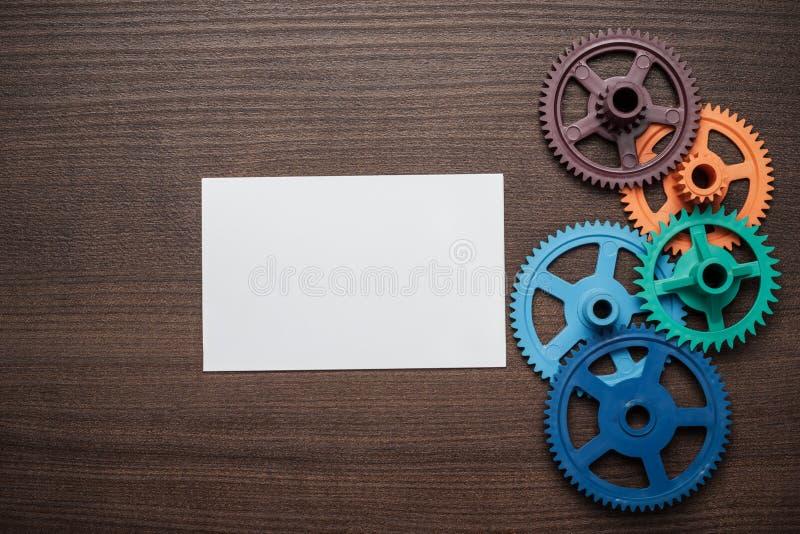 Красочные шестерни на коричневой деревянной предпосылке стоковое изображение
