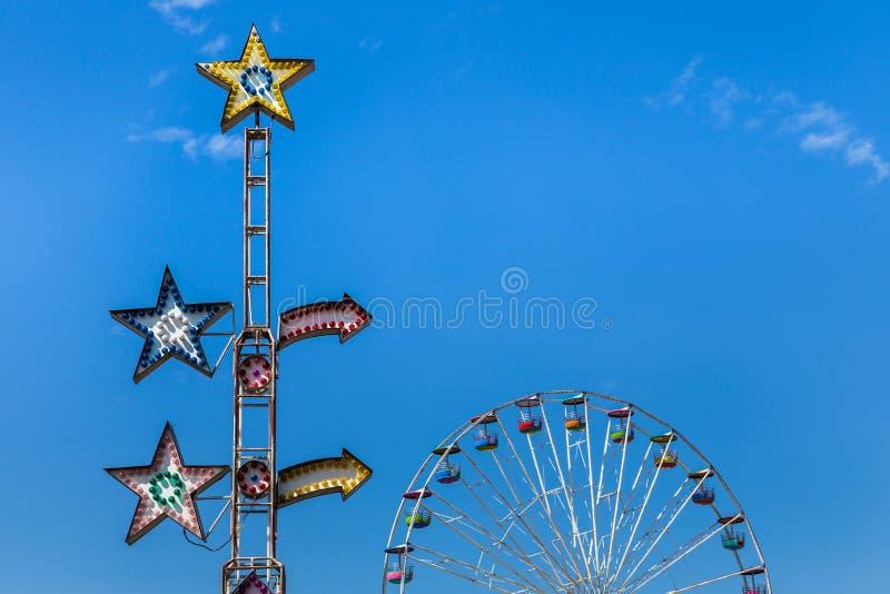 Красочные электрические лампочки езды масленицы с колесом ferris стоковая фотография rf