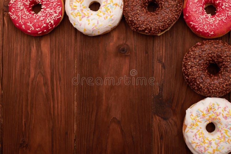 Красочные donuts лежа на коричневом деревянном столе стоковые изображения rf