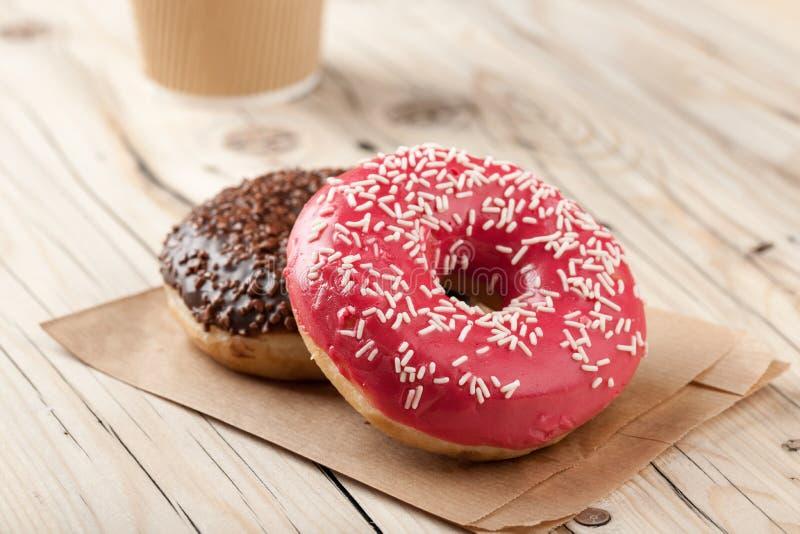 Красочные donuts и бумажный стаканчик на деревянном столе стоковое фото