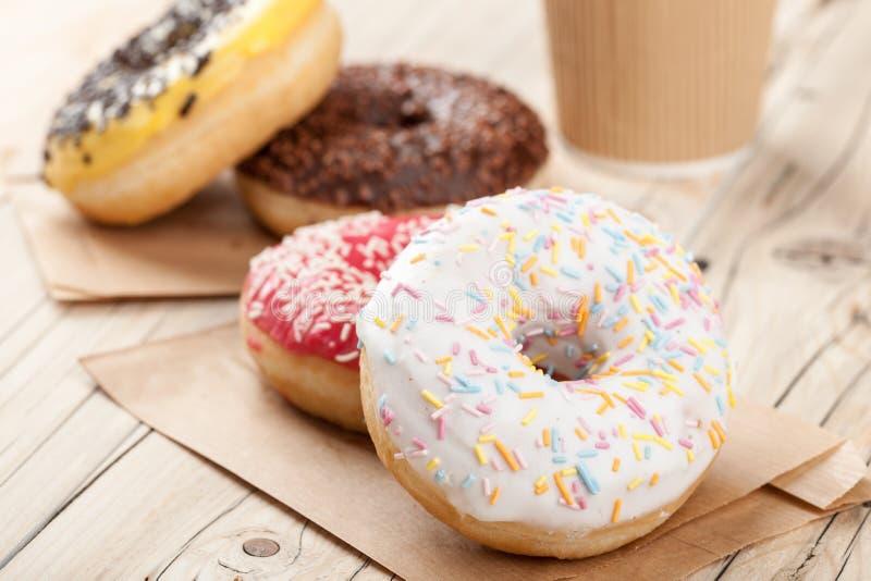 Красочные donuts и бумажный стаканчик на деревянном столе стоковая фотография rf
