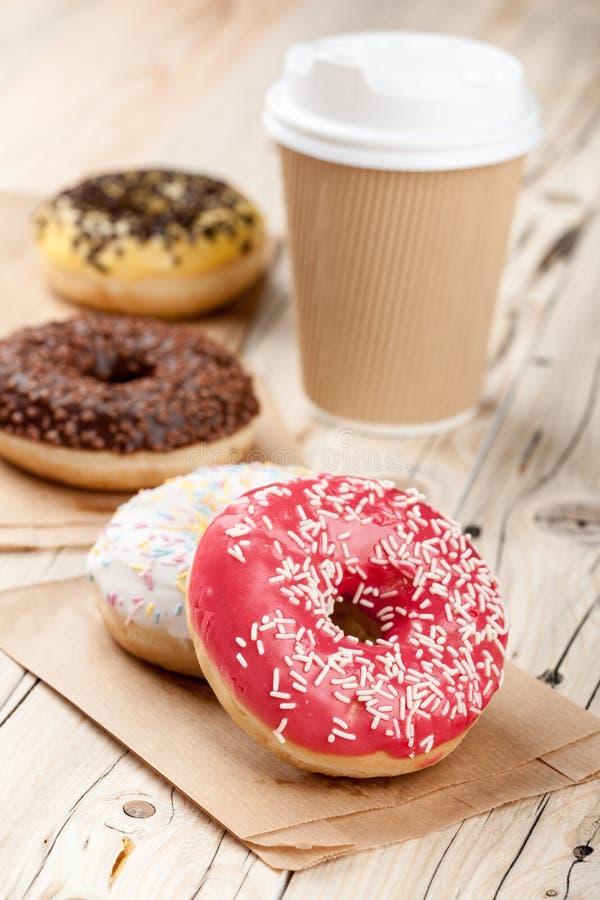 Красочные donuts и бумажный стаканчик на деревянном столе стоковое изображение