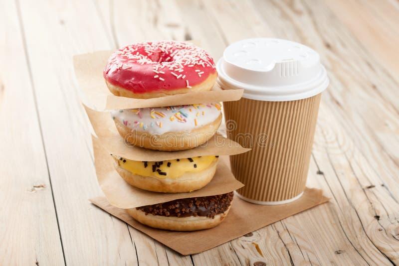 Красочные donuts и бумажный стаканчик на деревянном столе стоковые изображения