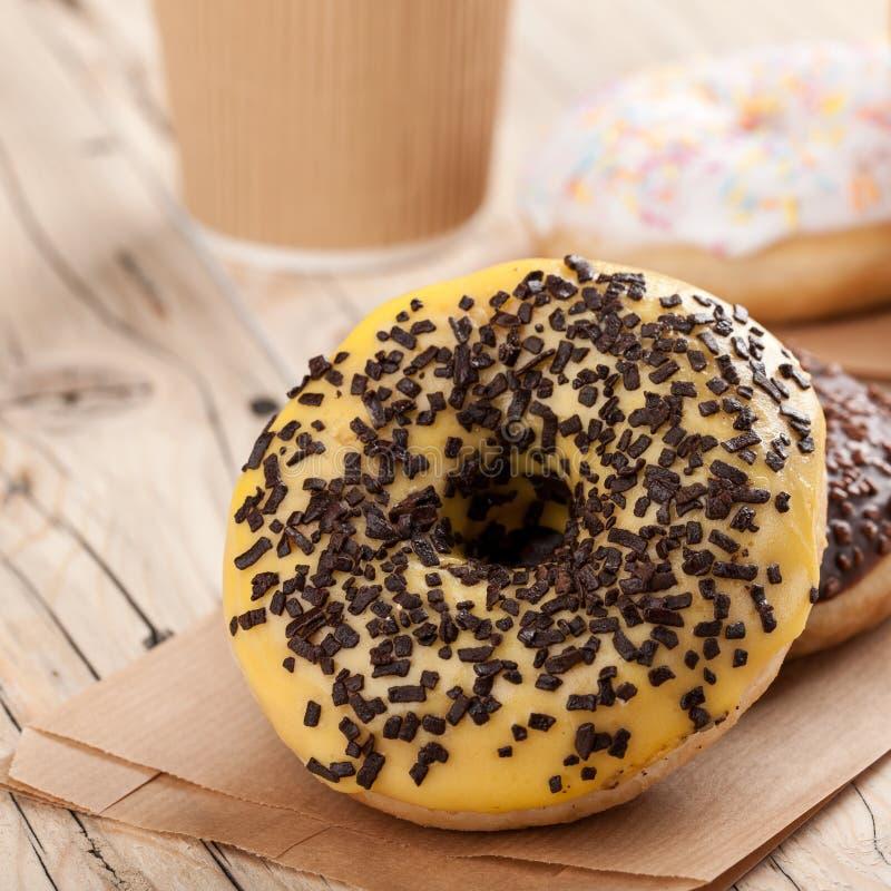 Красочные donuts и бумажный стаканчик на деревянном столе стоковые фото