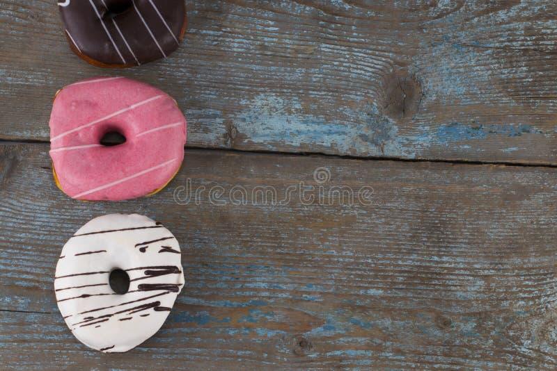 Красочные donuts на деревянной предпосылке Открытый космос для текста top стоковое фото