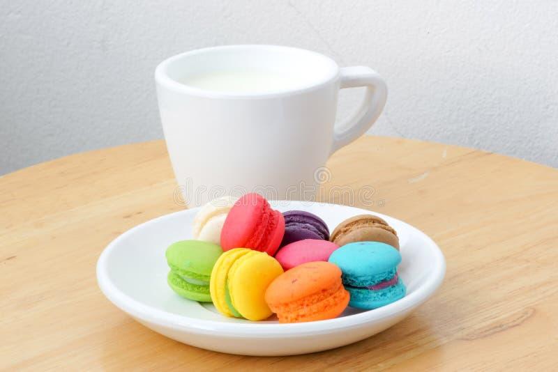 Красочные macarons и чашка молока стоковые изображения