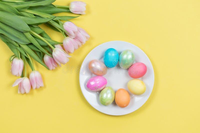 Красочные pearlescent пасхальные яйца и розовые тюльпаны стоковая фотография