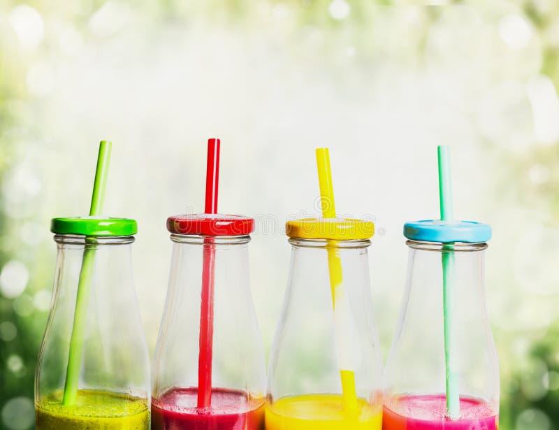 Красочные smoothies выпивают в бутылках с соломами на зеленой предпосылке природы стоковые фото