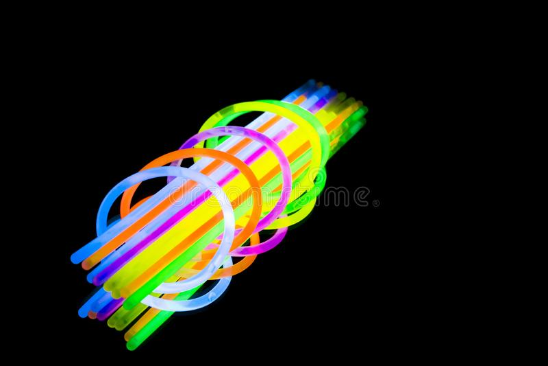 Красочные wristband и трубки ремня браслета ручки зарева дневного света неоновые на отражении зеркала чернят предпосылку иллюстрация штока