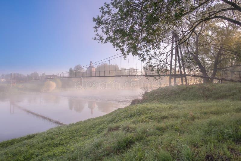Красочный взгляд церков и висячего моста от противоположного банка реки стоковые фото