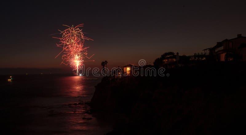 Красочный взрыв фейерверков над изумрудным пляжем залива стоковые фотографии rf