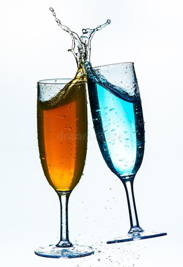 Красочный выплеск в стекле шампанского изолированном на белой предпосылке стоковая фотография
