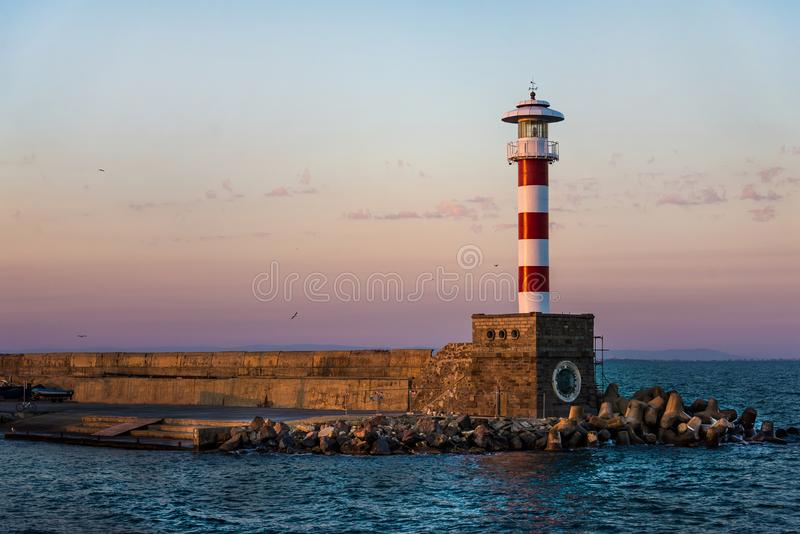 Красочный заход солнца над маяком берега моря Bourgas стоковые фото