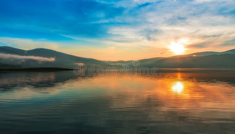 Красочный заход солнца над озером горы стоковые изображения