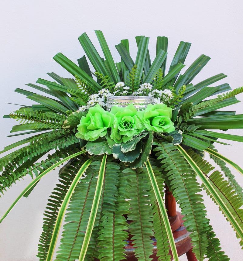 Красочный зеленый цвет букета искусственных цветков поднял, листья папоротника и ладонь на белой предпосылке бетонной стены стоковые изображения