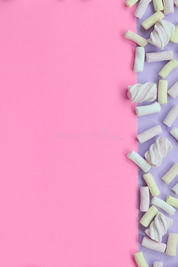 Красочный зефир положенный вне на фиолетовую и розовую бумажную предпосылку пастельные творческие текстурированные рамки минималь стоковая фотография
