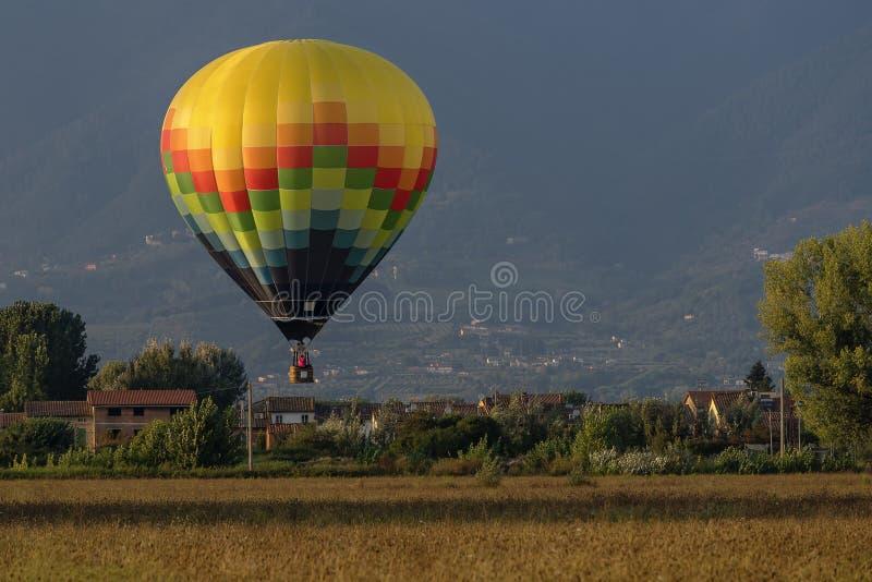 Красочный использующий горячий воздух воздушный шар летает над типичной деревней в тосканской сельской местности в свете захода с стоковое изображение rf