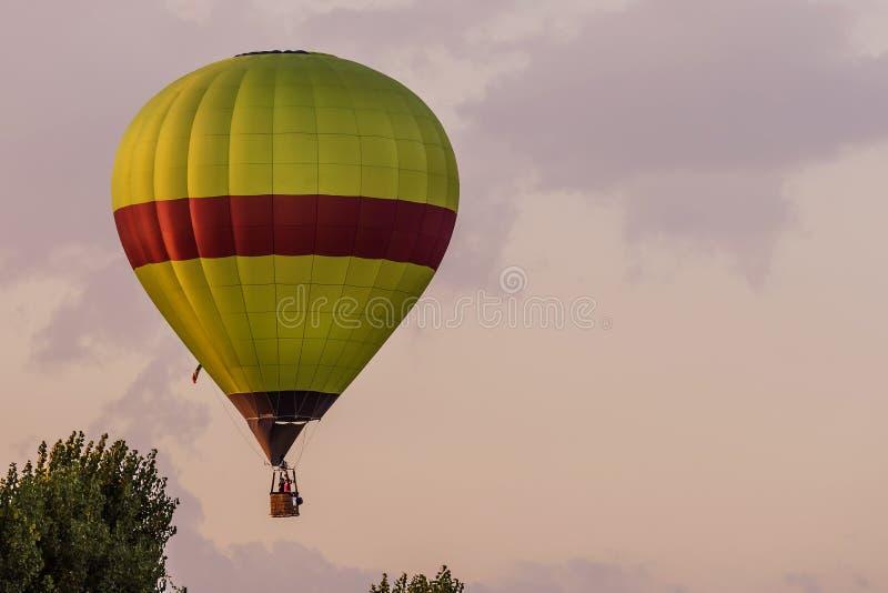 Красочный использующий горячий воздух воздушный шар летает над типичной деревней в тосканской сельской местности в свете захода с стоковые фото