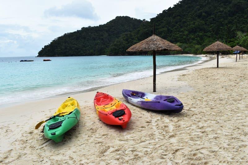 Красочный каяков стойте на песчаном пляже в каникулах Справочная информация стоковое фото