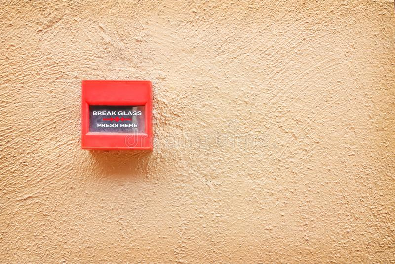 Красочный красный переключатель пожарной сигнализации на коричневой бетонной стене, ломая стеклянную предпосылку знака стоковое фото rf