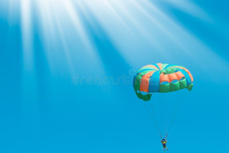 Красочный парашют на предпосылке голубого неба Красивый солнечный свет wiyh предпосылки лета Активный праздник на каникулах Здоро стоковая фотография