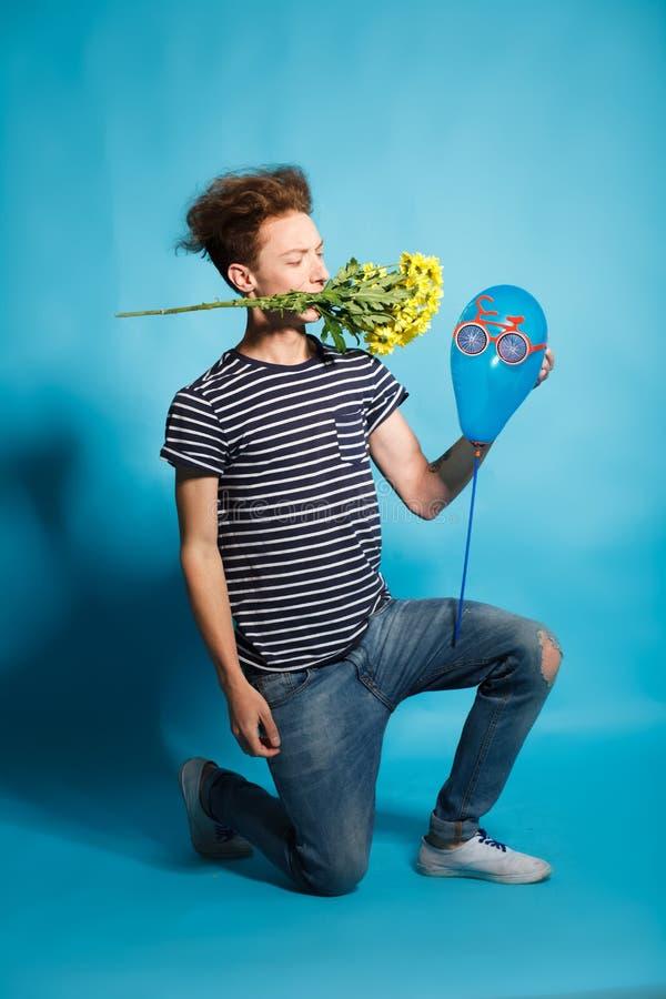 Красочный портрет молодого смешного человека представляя на голубой стене стоковая фотография