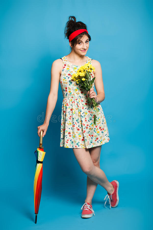 Красочный портрет молодой смешной девушки представляя на голубой стене стоковые изображения
