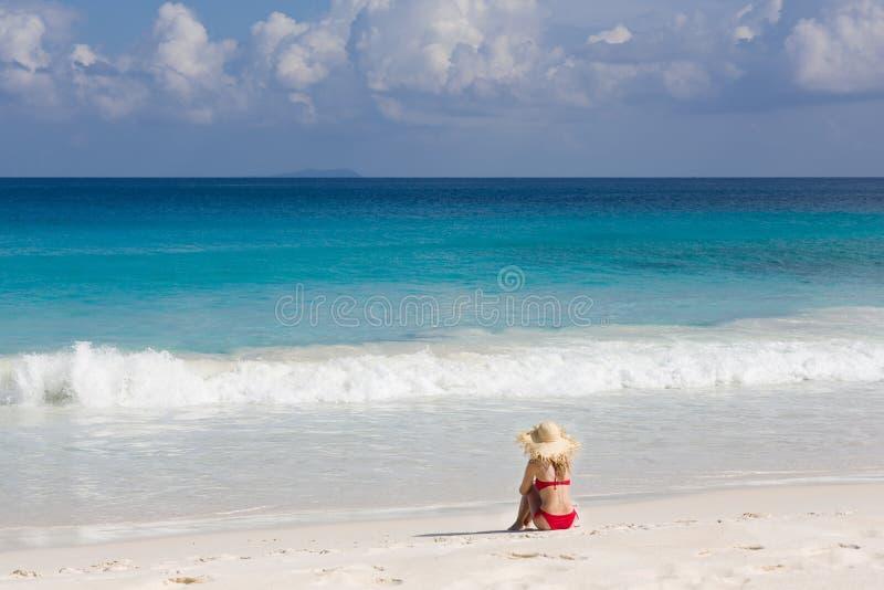 Красочный пляж океана, тонкая женщина в красном купальнике и солома греют на солнце шляпа стоковое изображение rf