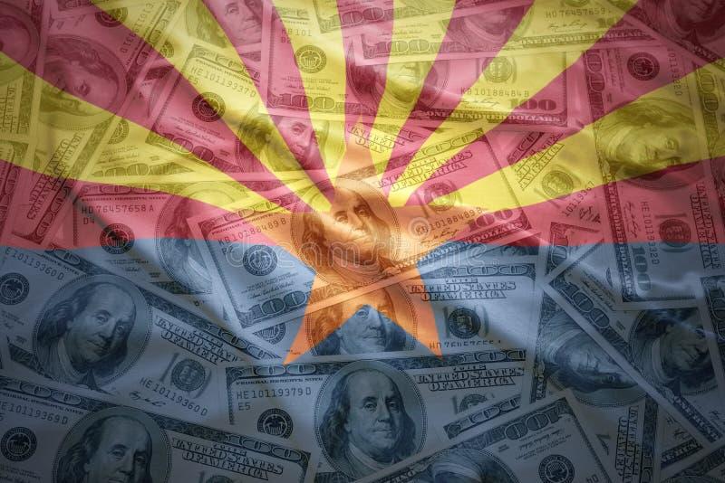 Красочный развевая национальный флаг Аризоны на американской предпосылке денег доллара стоковые изображения