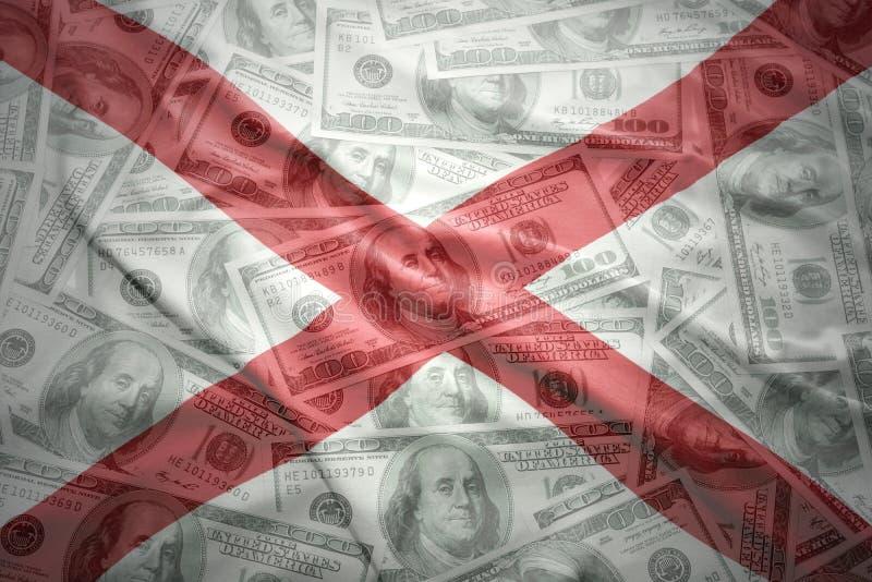 Красочный развевая национальный флаг Алабамы на американской предпосылке денег доллара стоковые фото