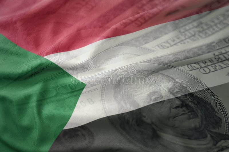 Красочный развевая национальный флаг Судана на американской предпосылке денег доллара стоковое фото