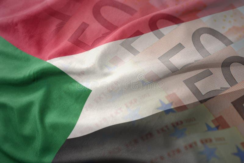 Красочный развевая национальный флаг Судана на предпосылке банкнот денег евро стоковое изображение rf
