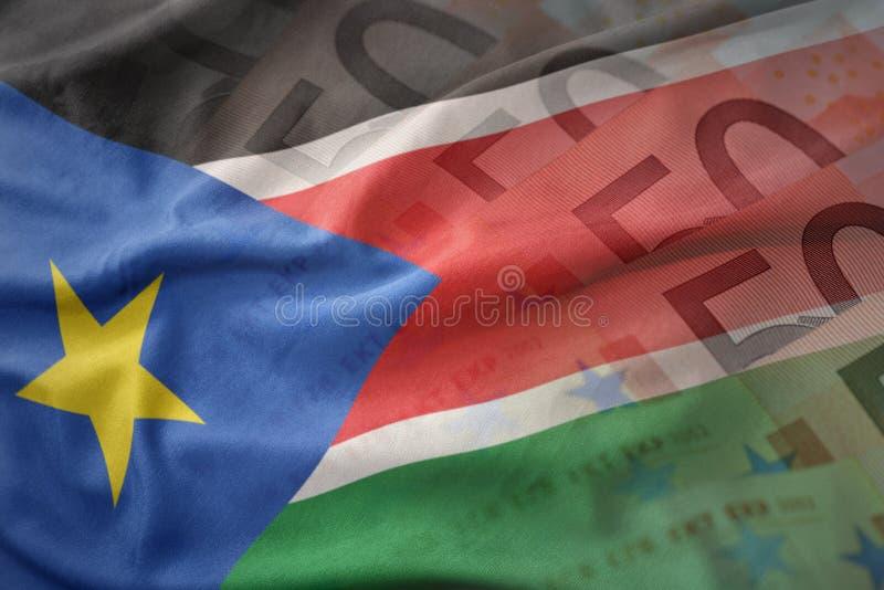 Красочный развевая национальный флаг южного Судана на предпосылке банкнот денег евро стоковое фото