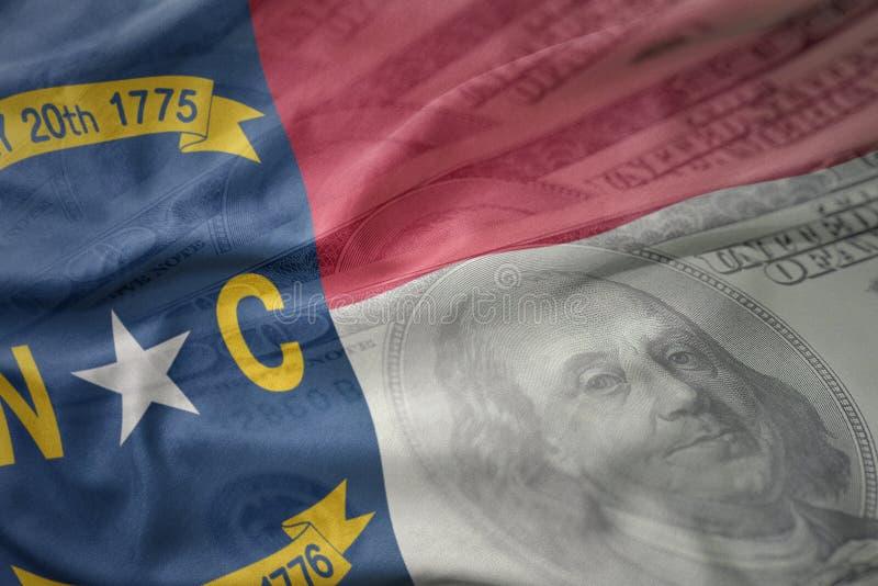 Красочный развевая флаг положения Северной Каролины на американской предпосылке денег доллара стоковые изображения