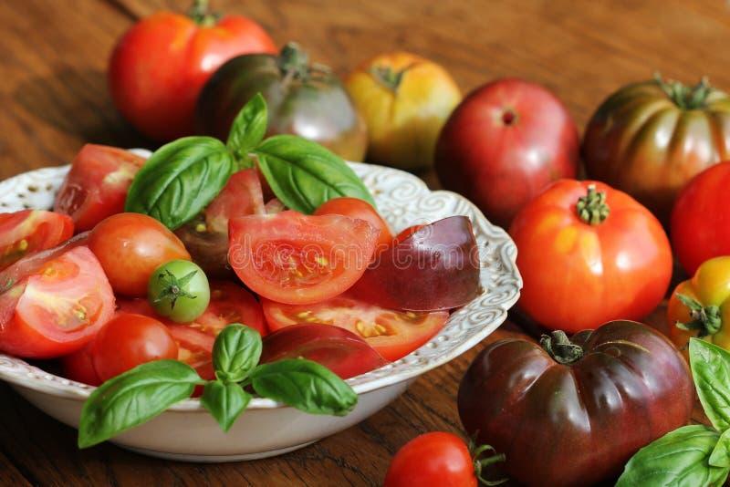 Красочный салат томатов с базиликом и бальзамический уксус на деревянной деревенской предпосылке стоковая фотография