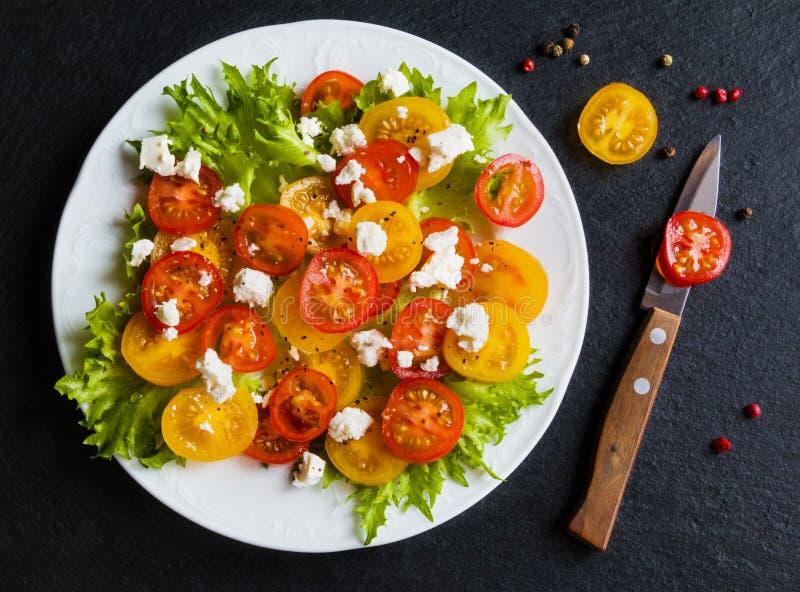 Красочный салат, свежие листья зеленого цвета и отрезанные красные и желтые томаты вишни, белая плита, нож, черная каменная предп стоковые фотографии rf