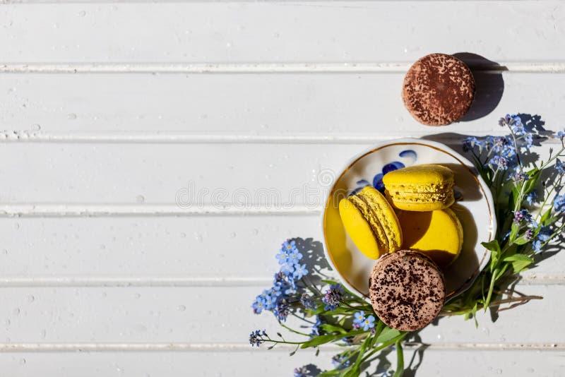 Красочный французский или итальянский стог macarons на белой плите положенной на деревянную таблицу с космосом экземпляра для пре стоковые фото