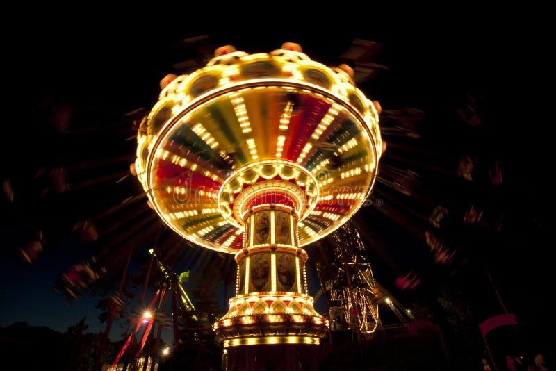 Красочный цепной carousel качания в движении на парке атракционов на ноче стоковая фотография rf