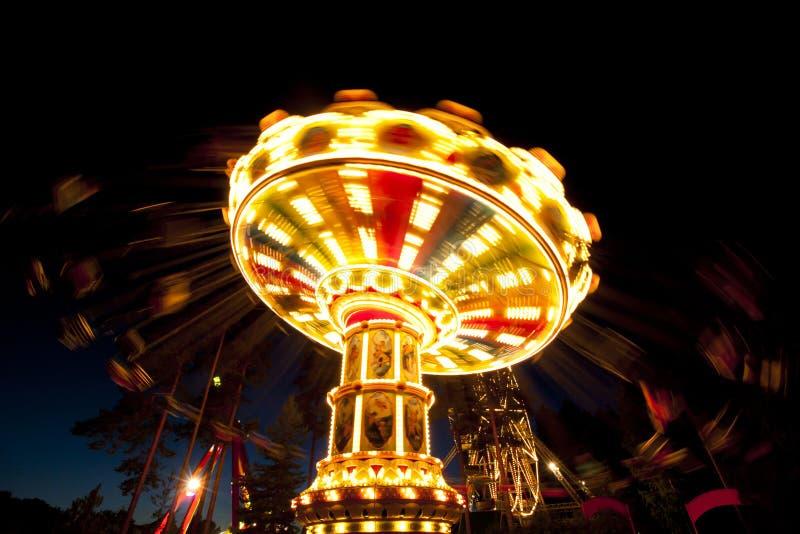 Красочный цепной carousel качания в движении на парке атракционов на ноче стоковые изображения