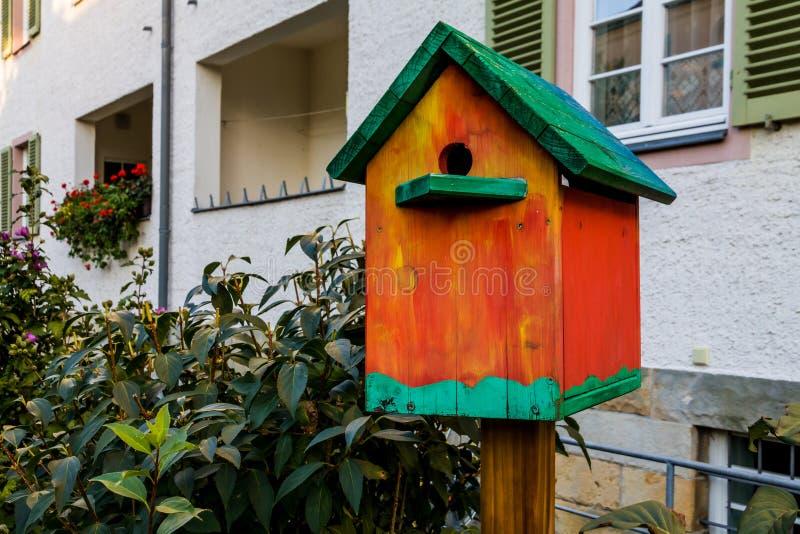 Красочный Birdhouse около дома стоковая фотография