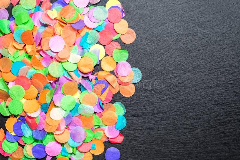 Красочный confetti на черном сланце как шаблон для торжества стоковое изображение rf